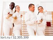 Купить «Smiling fencers posing with foils together at fencing room», фото № 32305399, снято 11 июля 2018 г. (c) Яков Филимонов / Фотобанк Лори