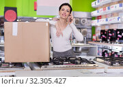 Купить «Female with packed purchases in store of household appliances», фото № 32305427, снято 21 февраля 2018 г. (c) Яков Филимонов / Фотобанк Лори