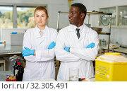 Купить «Experienced male and female scientists standing in laboratory», фото № 32305491, снято 21 марта 2019 г. (c) Яков Филимонов / Фотобанк Лори