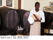 winemaker holding box with wine bottles standing in wine shop. Стоковое фото, фотограф Яков Филимонов / Фотобанк Лори