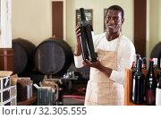 Купить «Smiling salesman in apron proposing wine in bottles in winery shop», фото № 32305555, снято 1 августа 2019 г. (c) Яков Филимонов / Фотобанк Лори