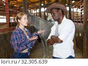Купить «Girl and man having emotional discussion at stable», фото № 32305639, снято 2 октября 2018 г. (c) Яков Филимонов / Фотобанк Лори