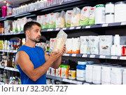 Купить «Man choosing food supplements in store», фото № 32305727, снято 7 апреля 2020 г. (c) Яков Филимонов / Фотобанк Лори