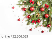 Christmas tree branch decorated with snowflakes, candy canes, bows and red Christmas balls. On white background. Стоковое фото, фотограф Юлия Бабкина / Фотобанк Лори