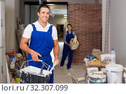 Man and woman in work overalls doing finishing work in room of public space. Стоковое фото, фотограф Яков Филимонов / Фотобанк Лори