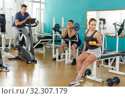 Купить «Girl and two men exercising in sport club», фото № 32307179, снято 5 ноября 2018 г. (c) Яков Филимонов / Фотобанк Лори