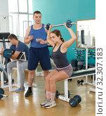 Купить «Trainer helping girl with exercise technique», фото № 32307183, снято 5 ноября 2018 г. (c) Яков Филимонов / Фотобанк Лори