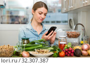 Portrait of glad woman looking at mobile phone while making dish on kitchen at home. Стоковое фото, фотограф Яков Филимонов / Фотобанк Лори