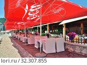 Купить «Budva, Montenegro - June 13.2019. Cafe beach in the resort area with red umbrellas with Coca Cola brand», фото № 32307855, снято 13 июня 2019 г. (c) Володина Ольга / Фотобанк Лори