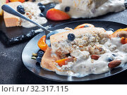 Купить «Italian summer dessert, a portion of melted Sicilian Almond apricot melon Semifreddo served on a black plate with fruits and berries, view from above, close-up», фото № 32317115, снято 21 июля 2019 г. (c) Oksana Zh / Фотобанк Лори