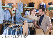 Купить «Smiling woman and man are choosing clothes and looking on jeans jacket», фото № 32317851, снято 12 марта 2018 г. (c) Яков Филимонов / Фотобанк Лори