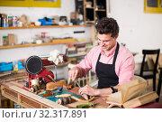 Купить «Craftsman in uniform working in carpentry», фото № 32317891, снято 8 апреля 2017 г. (c) Яков Филимонов / Фотобанк Лори