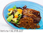 Купить «Tasty cooked fried pork with lentils, avocado and orange at plate», фото № 32318227, снято 28 января 2020 г. (c) Яков Филимонов / Фотобанк Лори