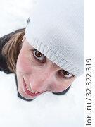 Close up view at women face looking up, brown eyes, white woollen hat on head, wide angle view. Стоковое фото, фотограф Кекяляйнен Андрей / Фотобанк Лори