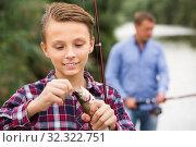 Купить «Teenage boy releasing catch on hook fish on lake», фото № 32322751, снято 6 декабря 2019 г. (c) Яков Филимонов / Фотобанк Лори