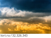 Dramatic blue thunderclouds on top and yellow-golden fluffy clouds illuminated by rays of sun on below. Stunning view natural meteorology background. Amazing cloudscape to weather change before rain. Стоковое фото, фотограф А. А. Пирагис / Фотобанк Лори
