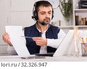 Купить «Young man call centre operator with headphones working», фото № 32326947, снято 25 декабря 2017 г. (c) Яков Филимонов / Фотобанк Лори