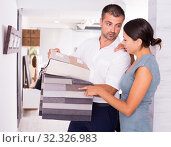 Купить «Couple looking for furnishing materials in store», фото № 32326983, снято 17 июля 2018 г. (c) Яков Филимонов / Фотобанк Лори