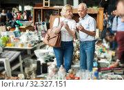 Купить «Mature family couple choosing vintage dishes on street market», фото № 32327151, снято 11 мая 2019 г. (c) Яков Филимонов / Фотобанк Лори