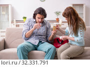 Купить «Young couple in first aid concept at home», фото № 32331791, снято 10 мая 2019 г. (c) Elnur / Фотобанк Лори