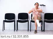 Купить «Young injured man waiting for his turn in hospital hall», фото № 32331855, снято 3 мая 2019 г. (c) Elnur / Фотобанк Лори