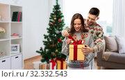 Купить «happy couple in christmas sweaters with gift box», фото № 32332543, снято 9 декабря 2018 г. (c) Syda Productions / Фотобанк Лори