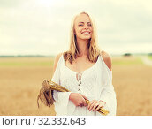 Купить «happy young woman with spikelets on cereal field», фото № 32332643, снято 31 июля 2016 г. (c) Syda Productions / Фотобанк Лори