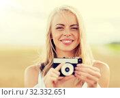 Купить «happy young woman with film camera outdoors», фото № 32332651, снято 31 июля 2016 г. (c) Syda Productions / Фотобанк Лори