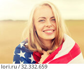 happy woman in american flag on cereal field. Стоковое фото, фотограф Syda Productions / Фотобанк Лори