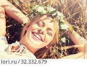 Купить «happy woman in wreath of flowers lying on straw», фото № 32332679, снято 31 июля 2016 г. (c) Syda Productions / Фотобанк Лори