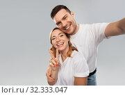 Купить «happy couple in white t-shirts taking selfie», фото № 32333047, снято 6 октября 2019 г. (c) Syda Productions / Фотобанк Лори