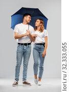 Купить «happy couple in white t-shirts with umbrella», фото № 32333055, снято 6 октября 2019 г. (c) Syda Productions / Фотобанк Лори