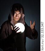 Купить «Young wizard with crystal ball in dark room», фото № 32333347, снято 25 августа 2017 г. (c) Elnur / Фотобанк Лори