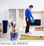 Купить «Young man collecting dirty clothing for laundry», фото № 32334815, снято 13 марта 2018 г. (c) Elnur / Фотобанк Лори