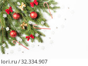 Купить «Christmas tree branch decorated with snowflakes, candy canes, bows and red balls with gold pattern», фото № 32334907, снято 19 октября 2019 г. (c) Юлия Бабкина / Фотобанк Лори