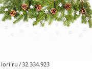 Купить «Winter Christmas border of fresh spruce branches decorated with pine cones and snowflakes, on white background», фото № 32334923, снято 19 октября 2019 г. (c) Юлия Бабкина / Фотобанк Лори