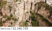 Купить «Aerial view of Ronda landscape and buildings with Puente Nuevo Bridge, Andalusia, Spain», видеоролик № 32340199, снято 18 апреля 2019 г. (c) Яков Филимонов / Фотобанк Лори