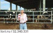 Купить «Portrait of successful young female breeder standing in cowshed», видеоролик № 32340331, снято 9 июня 2019 г. (c) Яков Филимонов / Фотобанк Лори