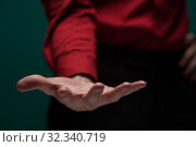 Купить «Young man in red shirt holds an invisible object», фото № 32340719, снято 14 апреля 2019 г. (c) Pavel Biryukov / Фотобанк Лори