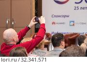 Купить «Мужчина в ярком красном свитере фотографирует на смартфон происходящее на сцене в конференц-зале», фото № 32341571, снято 25 октября 2019 г. (c) Наталья Николаева / Фотобанк Лори