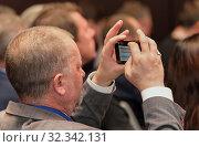 Купить «Мужчина в конференц-зале фотографирует на смартфон. Крупный план», фото № 32342131, снято 25 октября 2019 г. (c) Наталья Николаева / Фотобанк Лори