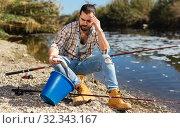 Купить «Upset fisherman displeased with fish catch», фото № 32343167, снято 15 марта 2019 г. (c) Яков Филимонов / Фотобанк Лори
