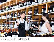 Купить «portrait of male seller showing bottle of wine to female customer in wine shop», фото № 32343383, снято 6 июня 2020 г. (c) Яков Филимонов / Фотобанк Лори