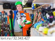 Купить «Portrait of adult man in jacket and helmet who is demonstrating ski and boots in store.», фото № 32343427, снято 31 июля 2017 г. (c) Яков Филимонов / Фотобанк Лори