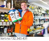Купить «Man 22-28 years old in helmet and jacket is demonstrating ski boots», фото № 32343431, снято 31 июля 2017 г. (c) Яков Филимонов / Фотобанк Лори