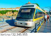 Купить «PORTO, PORTUGAL - JUNE 07, 2017: Train of Porto Metro on Dom Luis iron Bridge at sunset time. The network has 6 lines and reaches seven municipalities within the metropolitan Porto area.», фото № 32345955, снято 7 июня 2017 г. (c) age Fotostock / Фотобанк Лори