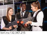 Купить «Smiling associates – afro man and two European women posing at laser tag room», фото № 32347215, снято 4 апреля 2019 г. (c) Яков Филимонов / Фотобанк Лори