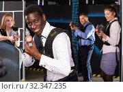 Glad Afro man and colleagues in laser tag room. Стоковое фото, фотограф Яков Филимонов / Фотобанк Лори