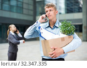 Young manager is talking phone and searching new job after dismissal. Стоковое фото, фотограф Яков Филимонов / Фотобанк Лори