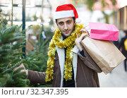 Купить «Young male in hat with purchases excited at Christmas market», фото № 32347395, снято 4 декабря 2018 г. (c) Яков Филимонов / Фотобанк Лори